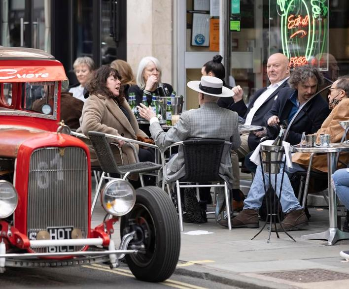 People enjoy an afternoon drink in the sunshine in London's Soho today as outdoor hospitality reopens