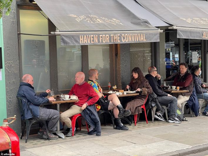 People eat outdoors in London's Soho this afternoon as they make the most of the warmer weather