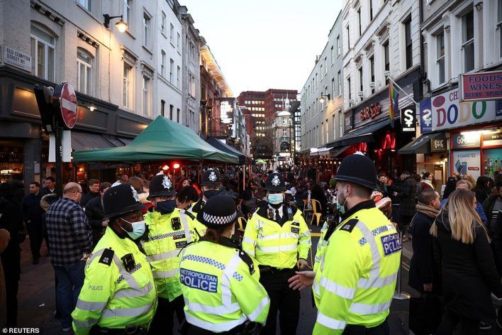 Police officers stand on the street next to people sitting at the terrace of a bar, as the coronavirus disease (COVID-19) restrictions ease