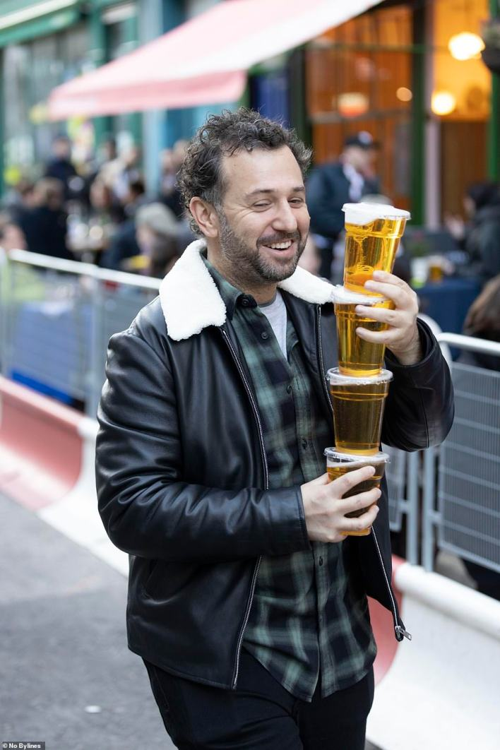 A reveller juggles multiple pints on a busy night of drinking in London after lockdown restrictions were finally eased