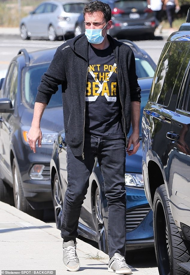 Sizzling: The 48-year-old Justice League idol looked laid-back California in a dark hoodie thrown over a t-shirt and teamed with dark jeans
