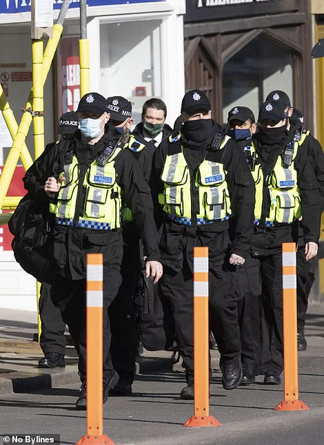 Police officers troop through the town of Windsor this morning ahead of Philip's funeral