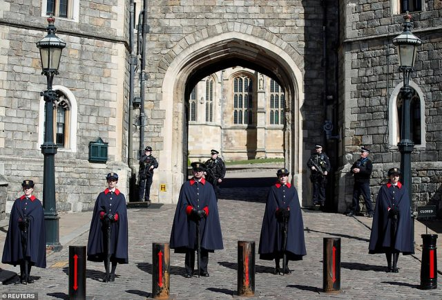 The wardens of Windsor Castle stand in front of the iconic archway leading into the grounds, where HRH Prince Philip will be laid to rest