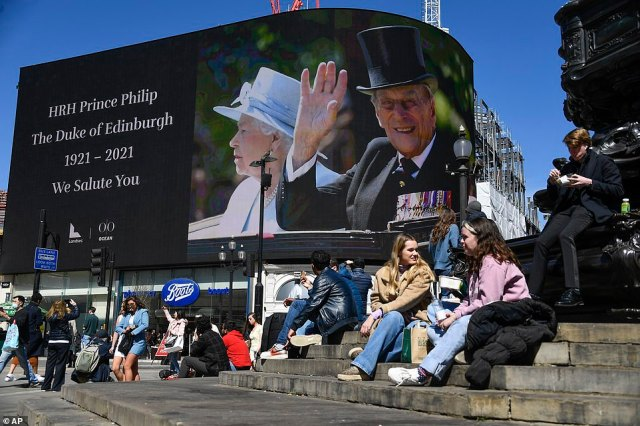 People sit near a screen displaying photos of the late Duke of Edinburgh, at Piccadilly Circus, in London this afternoon