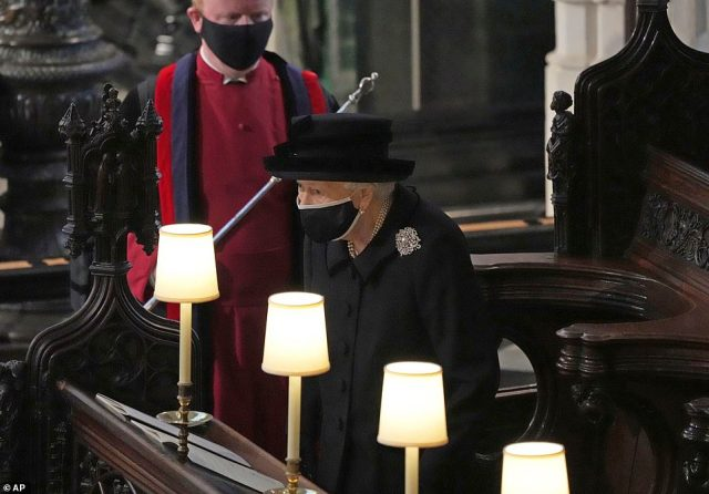 Queen Elizabeth II takes her seat alone in the quire of St. George's Chapel during the funeral of Prince Philip, the man who had been by her side for 73 years