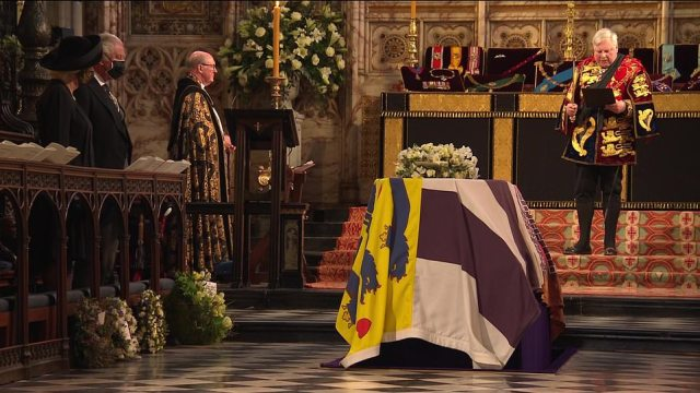 Prince Philip's flag-draped coffin in the centre of St George's Chapel as his family watch on during his funeral service this afternoon