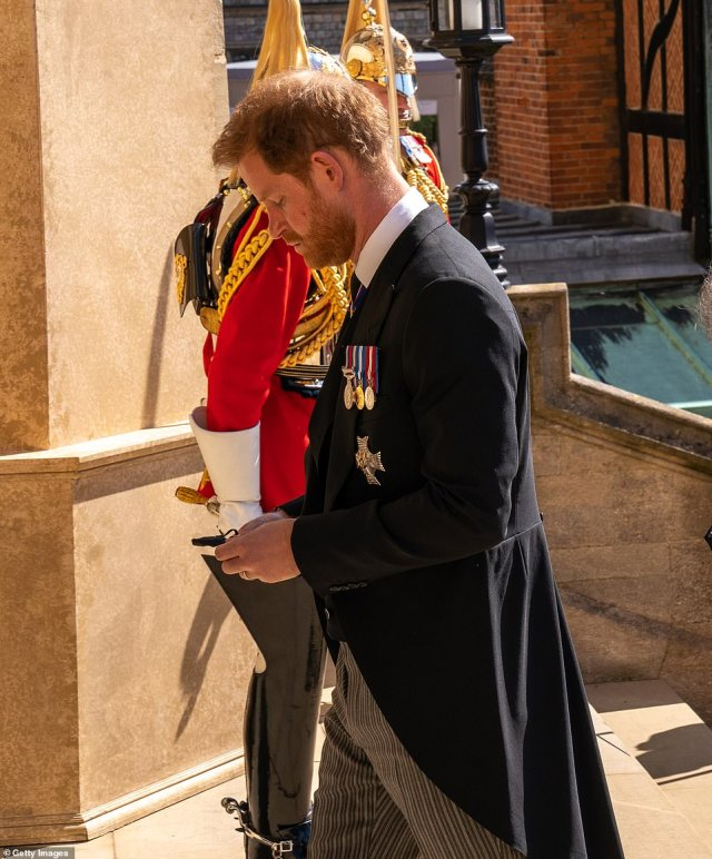 Prince Harry, Duke of Sussex holds his mask as he follows The Duke of Edinburgh's coffin into St George's Chapel