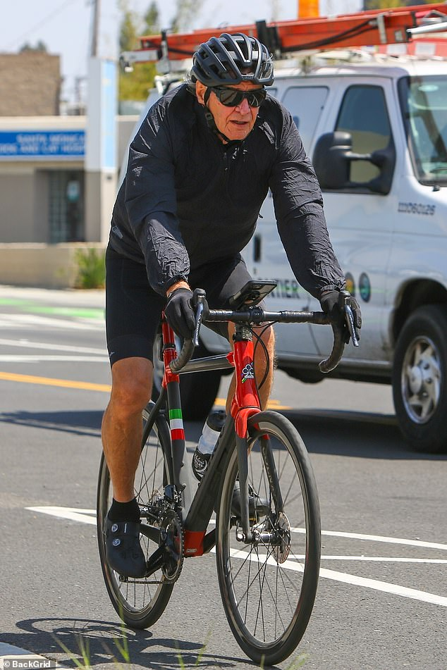 Hitting the street: Ford threw on a jacket, helmet and gloves as he trekked through the sunny streets of Los Angeles to get in his miles.He also wore a pair of bike shorts to hug his toned legs, and a pair of grey cycling shoes for the afternoon ride