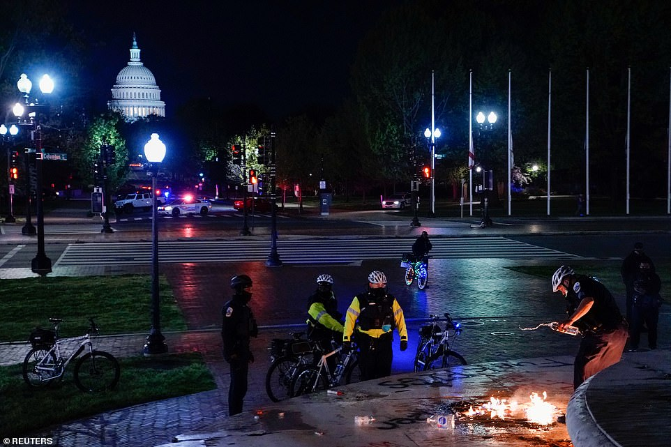 The U.S. Capitol Building is seen as police try to put out the fire from a flag during a demonstration in Washington, D.C.