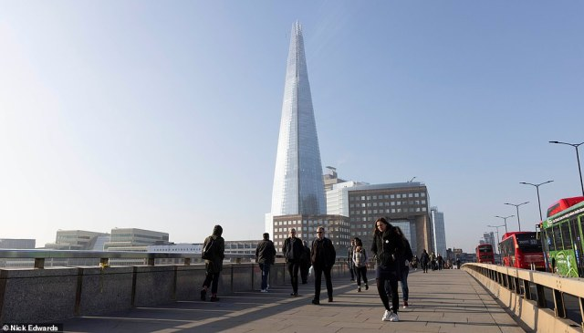 Much of the UK is set for a mini heatwave this week with temperatures set to reach 66F this afternoon. Pictured: commuters in London enjoy a warm and sunny walk across London Bridge this morning as the UK sees clear skies and warm temperatures