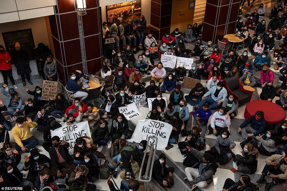 The students sat on the floor of the Ohio Union and held signs saying 'stop killing us' to protest against the latest shooting