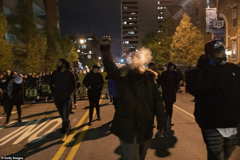 An activist raises their fist during a protest in reaction to the police shooting of Bryant in Columbus, Ohio