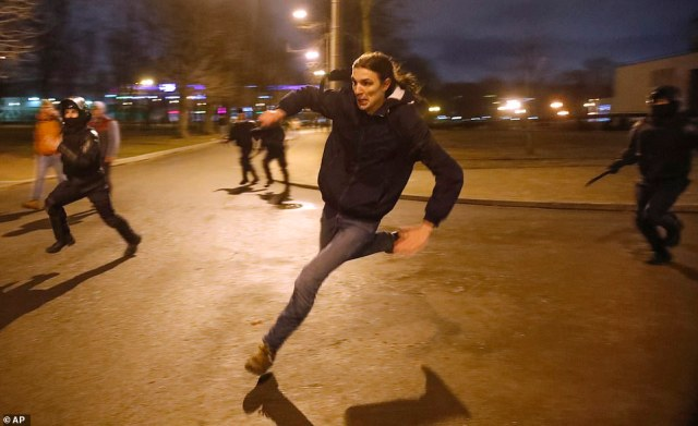 A demonstrator bolts away from police officers during an unsanctioned demonstration in support of Navalny on Wednesday