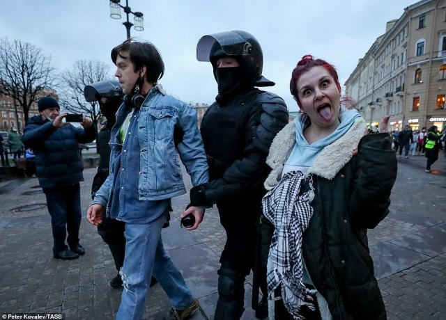 A man and a woman are led away by riot police in St Petersburg last night during pro-Navalny demonstrations