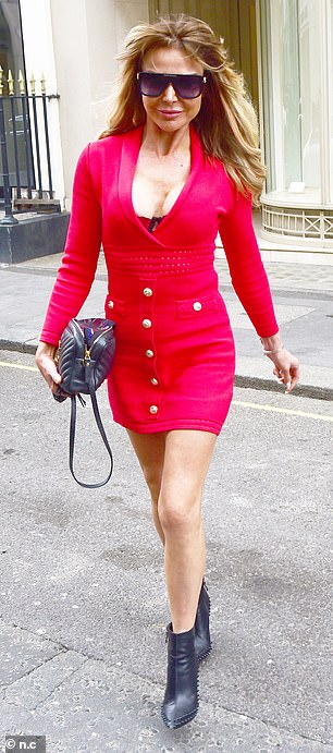 Don't mind me: Fully exposing her cleavage, the outfit inevitably commanded attention during a photo opportunity outside the Dover Street address