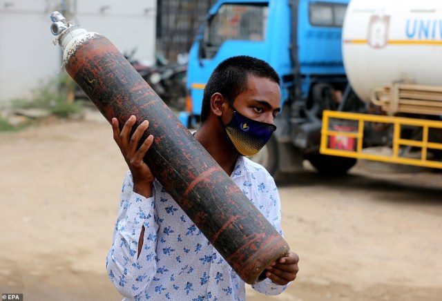 An Indian boy carries an empty oxygen cylinder for filling at oxygen filling centre in Bangalore on Wednesday