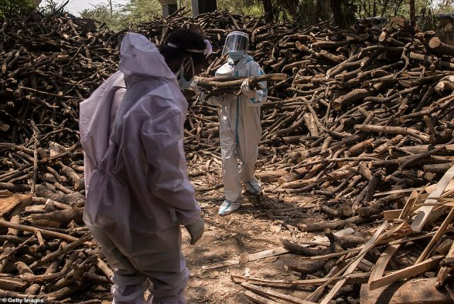 Cemetery workers in full PPE sort logs for the funeral pyres of the vast number of people dying from the coronavirus amid a severe second wave in India