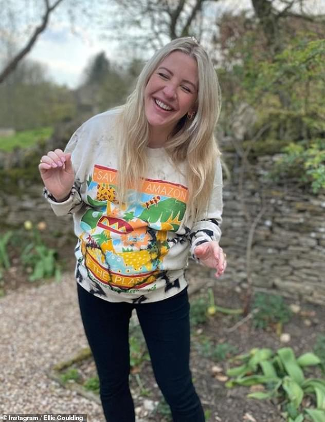 Merry: The musician, 34, cradled her baby bump in the cozy sweatshirt, which featured the words: 'Save our Amazon, save the planet'