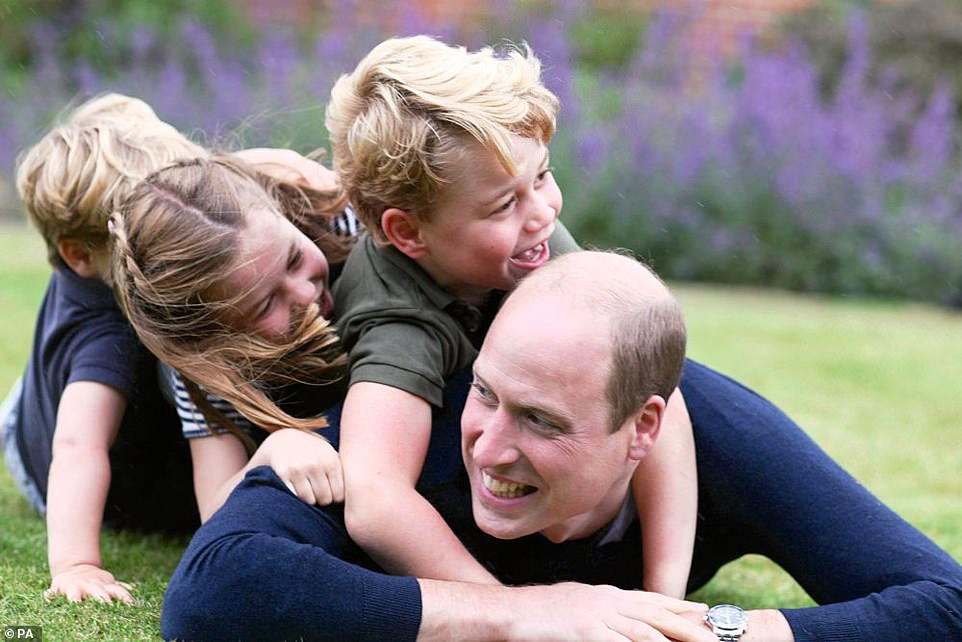 Prince William is seen playing with his three children in a photo released to mark both Father's Day and the Duke's birthday last year