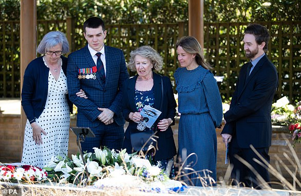 The family of D-Day veteran Albert Lilly look at flowers in the flower courtyard after his funeral service at The Oaks Havant Crematorium in Hampshire