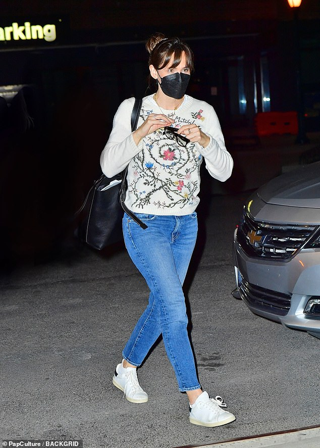 Jen's look:She completed her look with white sneakers and a large black purse, as she stepped outside while putting on her black-framed glasses