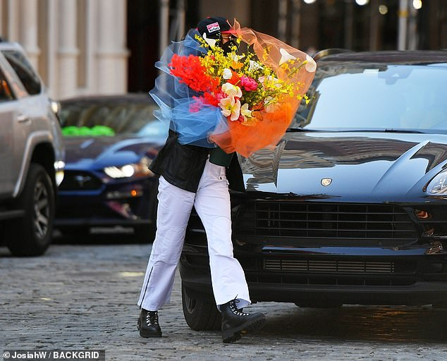 Stylish stroll: Bella made her way out of a Porsche with a custom bouquet