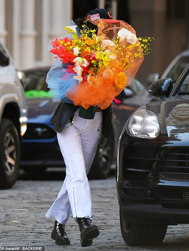 Happy colors: The model wore white pants as she brought a bouquet that was sure to make Gigi smile