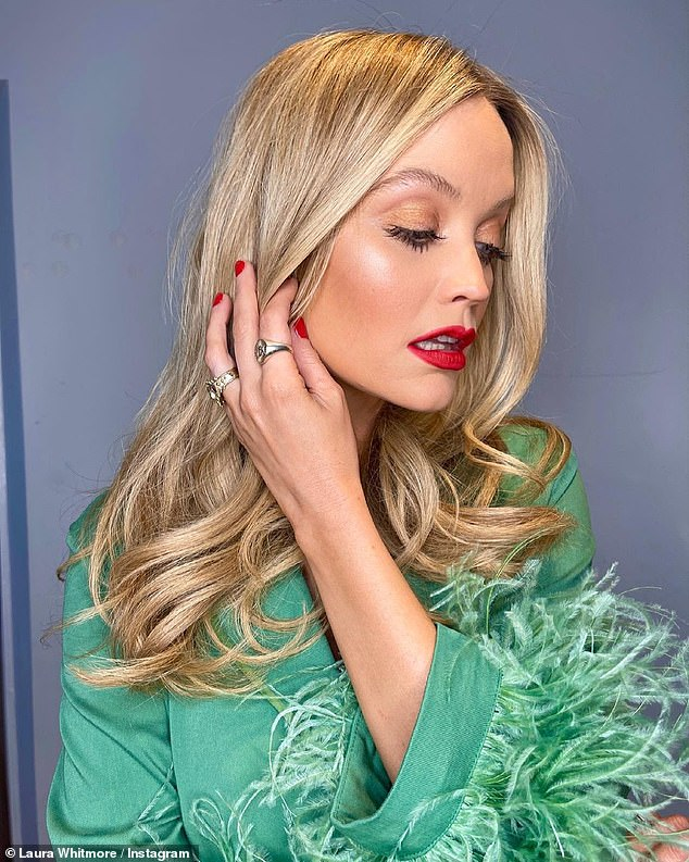 Glam:Laura wore her signature blonde locks in bouncy curls and sported a full face of make-up, including bronzed lids and a slick of bold red lipstick