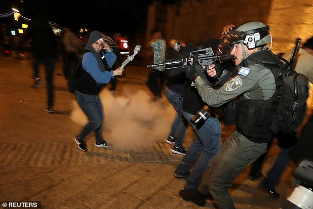 Palestinians say police have tried to prevent them from holding their usual Ramadan evening gatherings outside the gate, where metal barriers have been put up in its amphitheatre-style plaza. Israelis have been angered by videos on social media showing Palestinians assaulting religious Jews in the city. Pictured: Officer points a stun gun at protesters