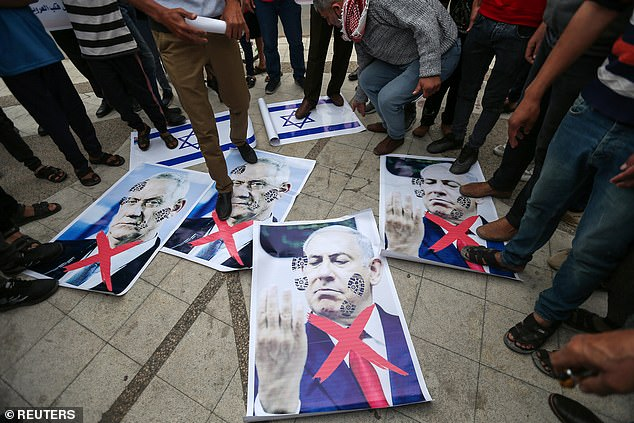 Pictured:Palestinians step on posters depicting Israeli Defence Minister Benny Gantz and Israeli Prime Minister Benjamin Netanyahu during an anti-Israel protest over tension in Jerusalem, in the southern Gaza Strip, April 24