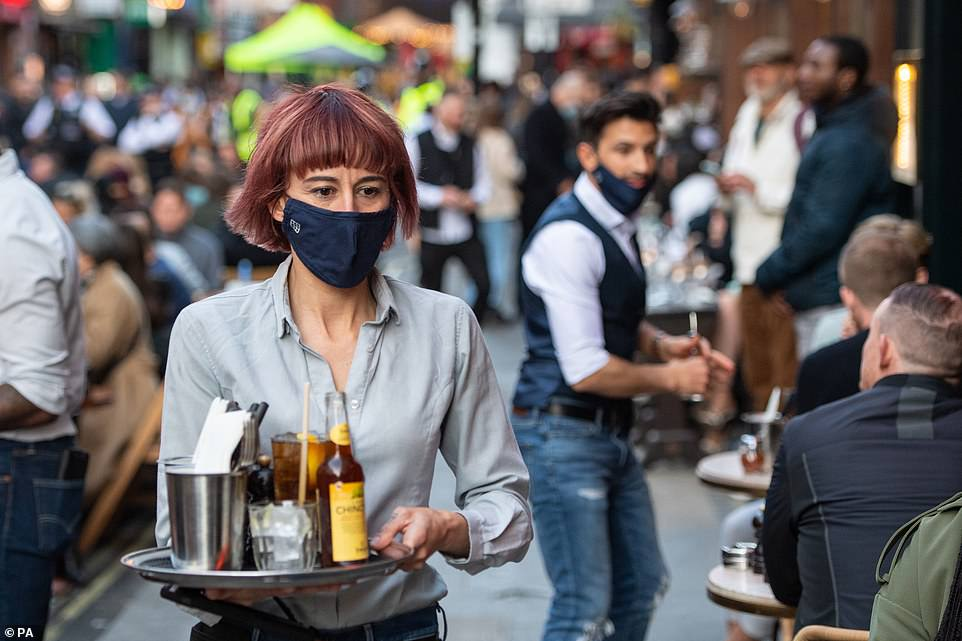 Pictured: Waiters serve people eating and drinking at outside tables on Saturday evening in Soho, central London