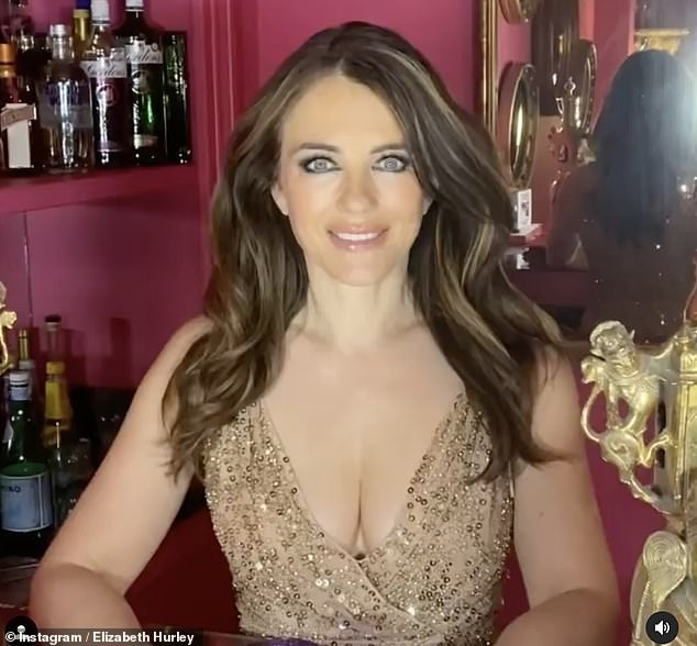 Sizzling:Elizabeth Hurley looked incredible in a plunging gold dress as she got ready to attend Elton John's 'legendary' Oscars party from home on Sunday night
