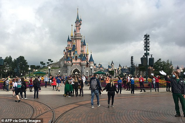 Visitors and staff wearing protective face masks, walk down the Main Street of Disneyland Paris in Marne-la-Vallee on the outskirts of Paris in July 2020