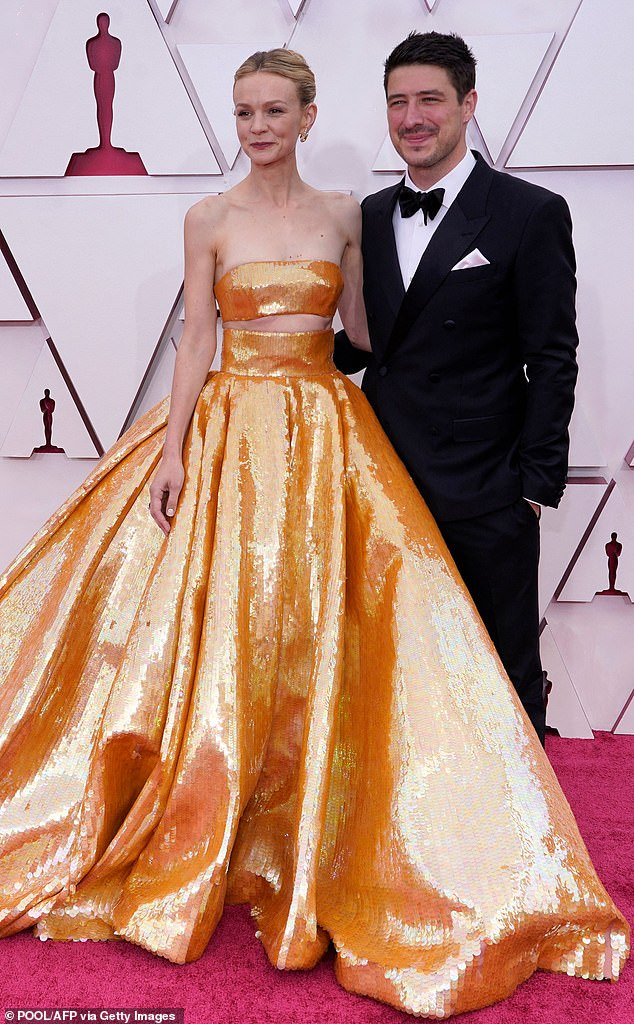 Golden girl! British actress Carey Mulligan (L) and husband US-British musician Marcus Mumford are seen posing on the red carpet at the Oscars at Union Station in Los Angeles