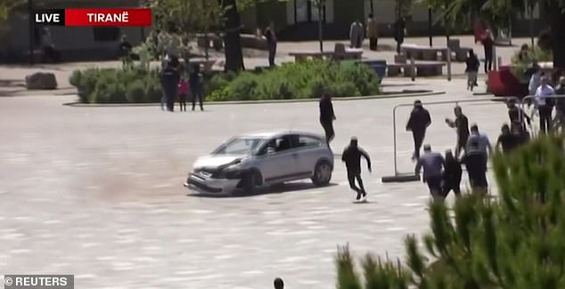 A member of the public runs towards the open window of a silver carin Skanderberg Square, Tirana, Albania, yesterday in an attempt to stop the driver who had been reversing at speed through a crowd of people