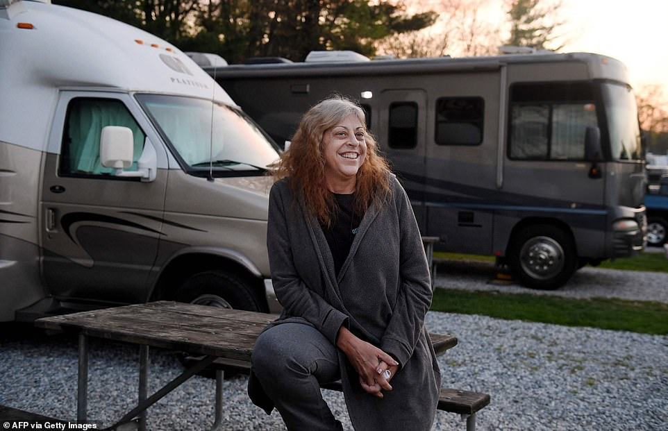 One woman pictured in the joyful snaps is Kathy Wardell (above), a 56-year-old who decided to live full-time in her van from October. She is seen beaming at the camera while posing by her home