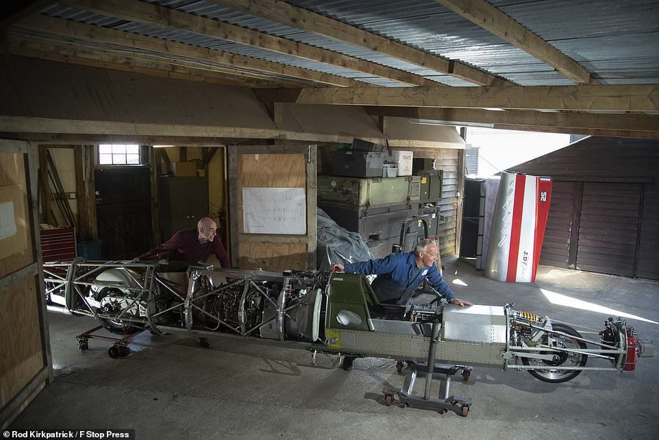 Mr Macfadzean has worked with engine builders for Formula One and Moto GP racing — and designed the vehicle that broke the 200 mph threshold in the British motorcycle land-speed record back in 1991. Pictured: Mr Macfadzean and design engineerAlastair Smith push the new streamliner racing motorcycle out of their workshop