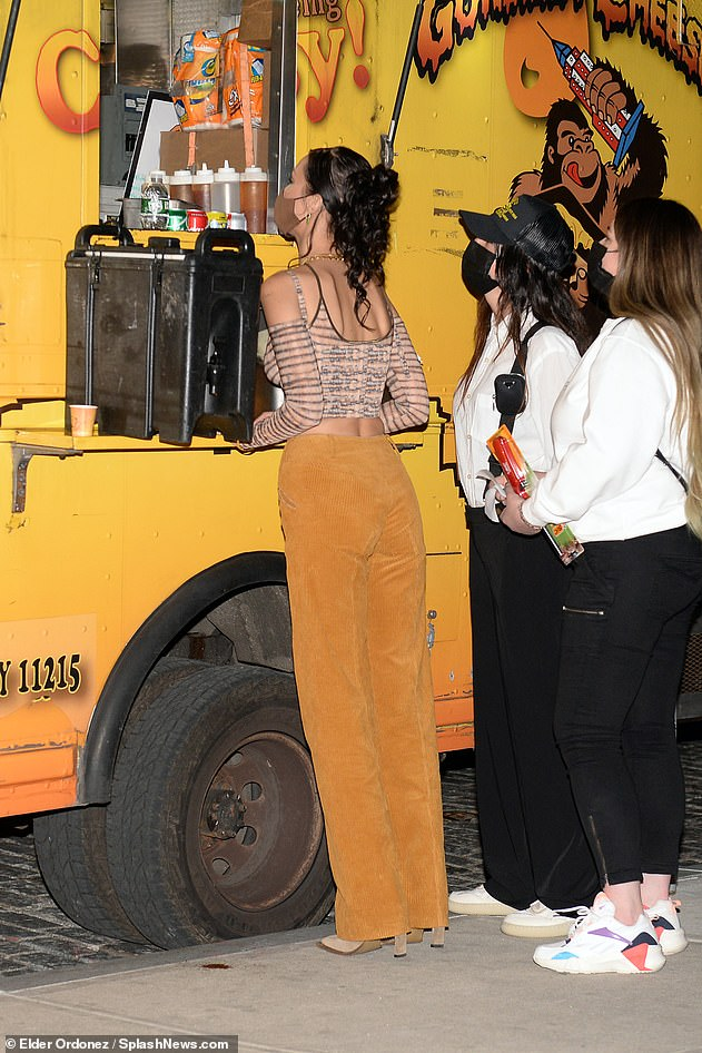 Food truck fun: Gigi paired the racy top with high-waisted orange velvet trousers that had a zipper detail in the front