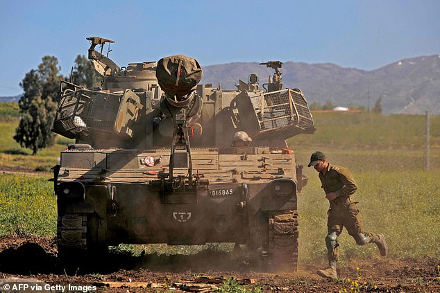 An Israeli soldier runs past a mobile artillery cannon at a position near Moshav Sha'al in the Israeli-annexed Golan Heights on April 22, 2021