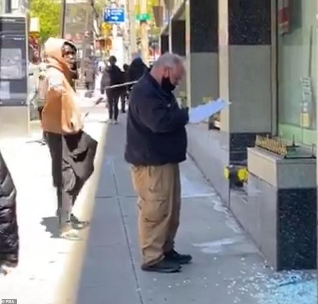 A man in an orange hoodie, named by police asAkeele Morgan, 25, of the Bronx, hits an officer on the head