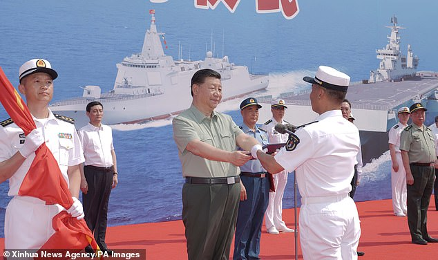 Chinese President Xi Jinping presides over a ceremony on Friday, unveiling three new warships set to patrol the South China Sea