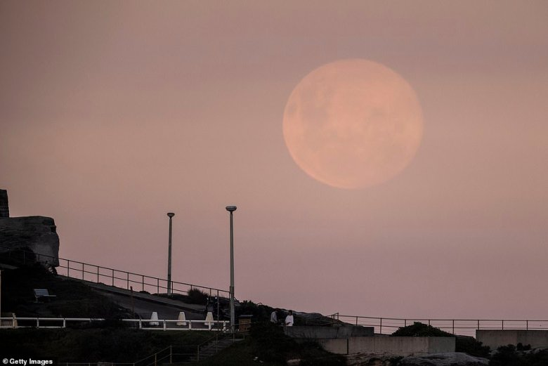 Locals walking by the beach could be seen stopping to gaze up at the rare full moon as it carve a huge orb on the horizon