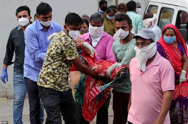 Relatives carry a woman who fainted after seeing the body of her husband at a government COVID-19 hospital in Ahmedabad