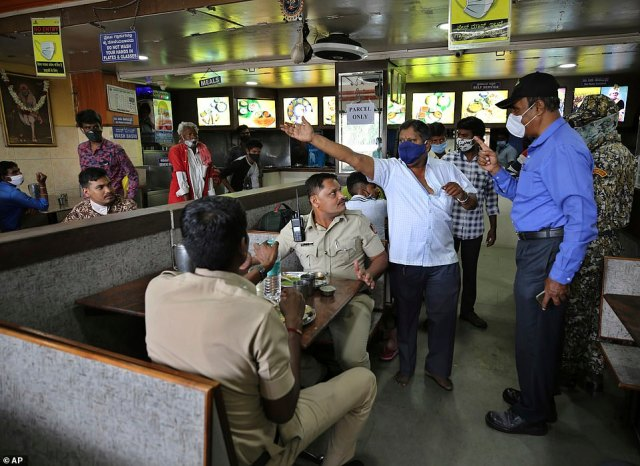 A municipal official, right in blue, reprimands a restaurant owner, in white for not adhering to guidelines during a lockdown imposed due to rising number of COVID-19 cases in Bengaluru