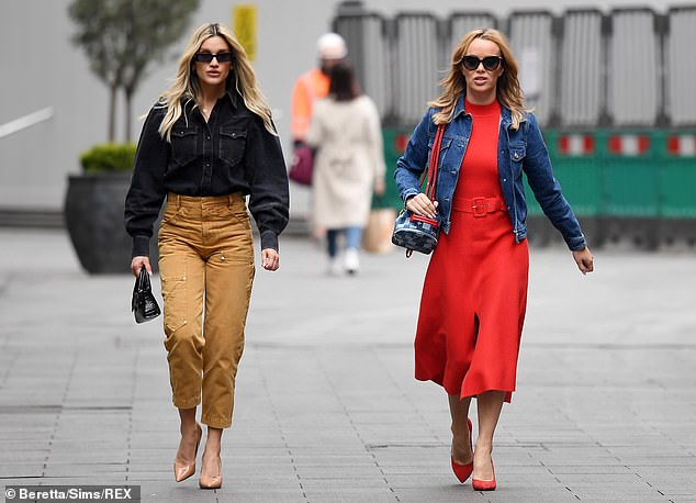 Gorgeous:Amanda (pictured right) highlighted her svelte physique in the form-fitting red midi dress with a belted waist and a slight leg split