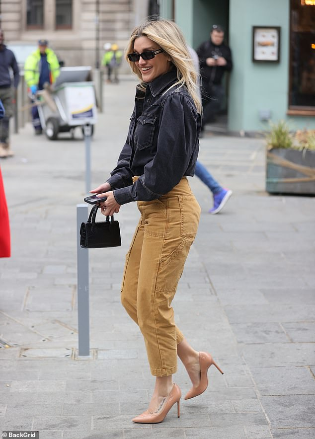 Standing out: She accessorised her look with narrow-framed sunglasses and a miniscule handbag