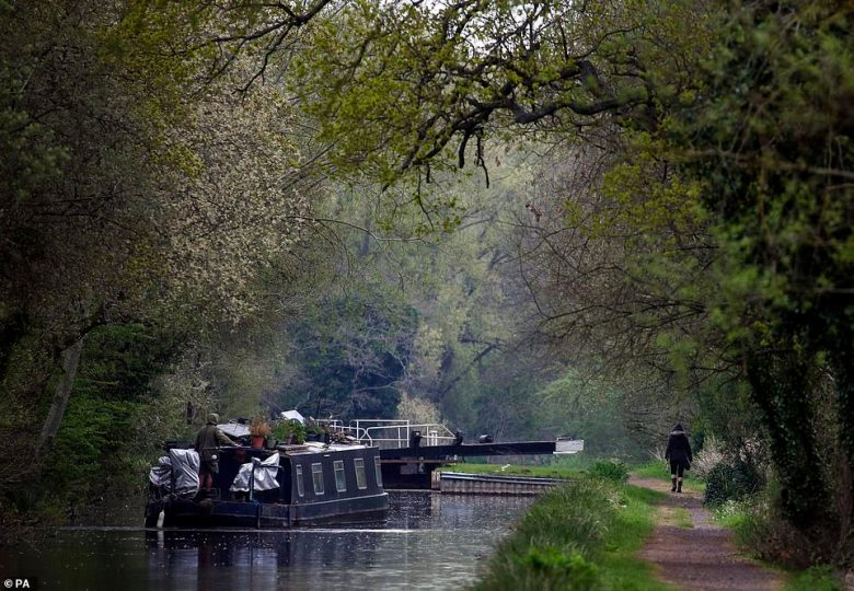 A canal boat travels in the rain along the River Kennet near Theale, Berkshire today