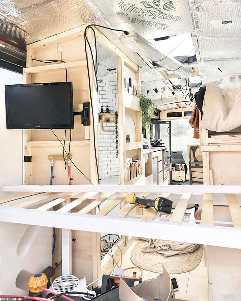 The family spent £13,000 on renovations including solar panels, a £4,000 electrical system, fridge, sink, cooker, heater and upholstery. Pictured:The Paige family bus in the middle of its revamp