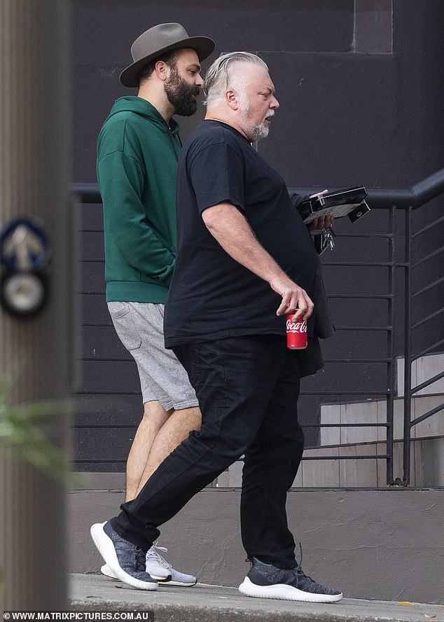 Chin wag: Kyle had a rather serious expression on his face as he sipped a can of Coca-Cola on a stroll with his manager Bruno Bouchet