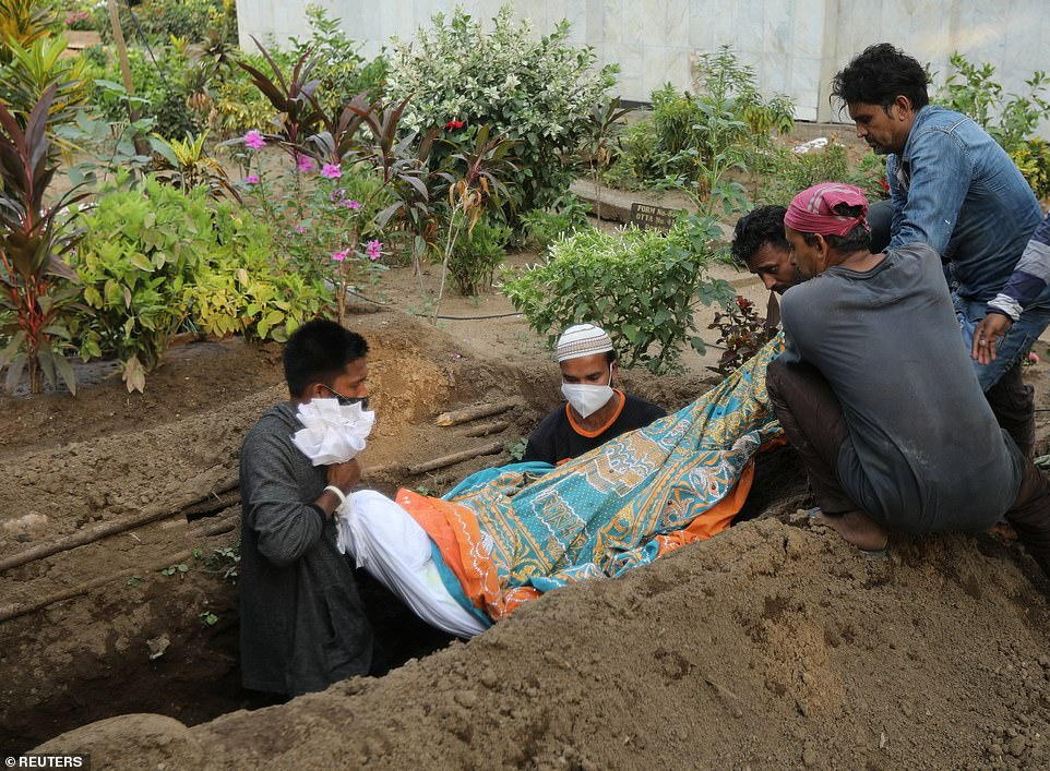 Gayesh Ansari watches as the body of his eight-months-pregnant wife Gulshan is lowered into a grave in Mumbai, India, after she died of Covid amid the country's brutal second wave